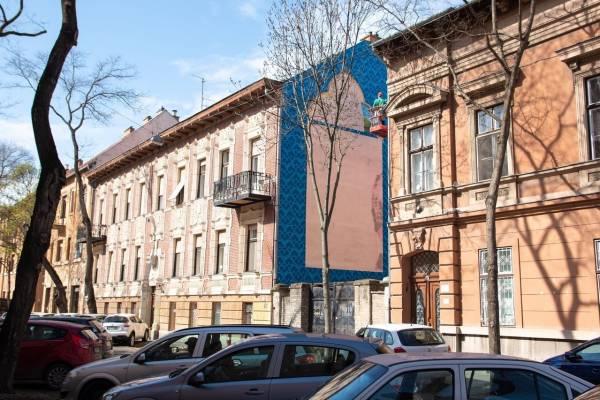 Szeged: A zsinagóga egyik díszes ablakának mintáit festik egy tűzfalra